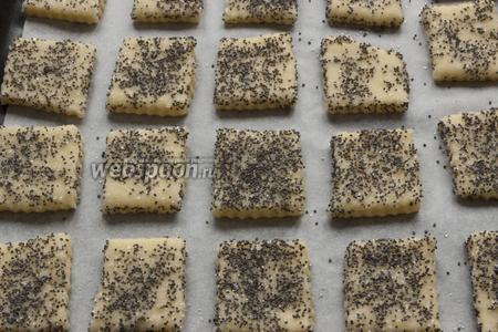 Каждое печенье «окунуть» одной стороной. Выложить на противень, застеленный пергаментной бумагой.