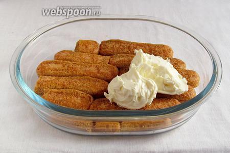 Печенье быстро обмакивать в пропитку только сахарной стороной и выкладывать в форму пропитанной стороной вверх. Смазать нижний слой кремом.