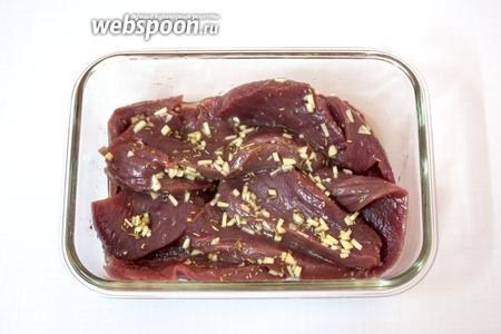 В миске смешаем мелко нарезанный чеснок, масло, розмарин. Посолим, поперчим. Выложим мясо. Хорошо обваляем. Оставим мариноваться на час.