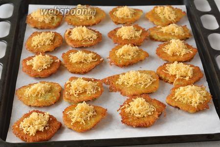 Форму для выпечки выложить кулинарной бумагой. На бумагу выложить драники, а на них горкой — тёртый сыр.