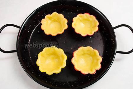 Поставить формы с тестом на противень. Поместить его в горячую духовку. Выпекать 15-20 минут при температуре 180°C. Через 5 минут после начала выпечки, открыть духовку и рюмкой примять донышко корзинки.