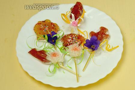 Заворачиваем леденцы в тонкую пищевую упаковочную плёнку, украшаем бантиками, цветочками или чем подскажет фантазия. С противоположной банту стороны под ленточку зацепляем скрепку, с помощью которой будем вешать леденцы на ёлку. Наше сладкое украшение готово!