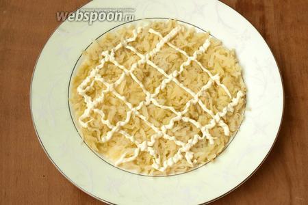 Третью часть картофеля выложить на блюдо в форме круга, сделать майонезную сеточку. Можно немного посолить.