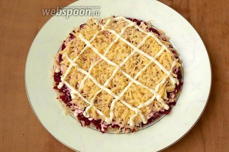 Натереть на тёрке твёрдый сыр. Частью сыра выложить слой поверх свеклы, покрыть майонезом.