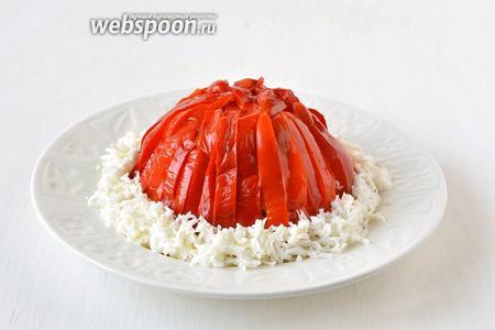 Украсить салат сверху полосками из маринованного сладкого перца. Ободок «шапочки» сделать из натёртого на средней тёрке белка варёного яйца.