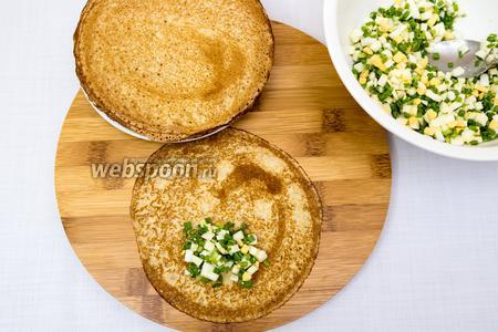 Яйца отварим.  В миске смешаем нарезанные мелкими кубиками яйца и лук. Посолим. Начинку выкладываем на блин и сворачиваем.