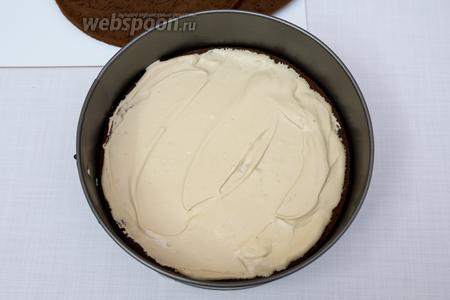 Дно разъёмной формы застелить пекарской бумагой. Выкладываем 1-й корж. Смазываем кремом. Затем: второй корж — крем.
