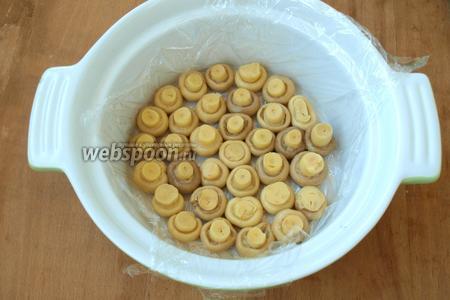 Взять подходящую форму для формирования салата, застелить её пищевой плёнкой, выложить шампиньоны шляпками вниз.