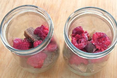 Нарежьте бисквит на кубики, разложите по стеклянным баночкам, сверху выложите малину. Ягоды лучше не размораживать, они дадут свой сок и бисквит хорошо пропитается.