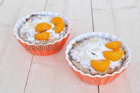 Присыпать сахарной пудрой и миндальными лепестками. Украсить консервированными мандаринами или свежими. Подавать горячей.