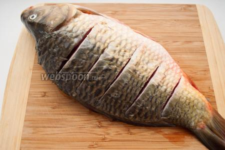 Промокните рыбу бумажным полотенцем и сделайте несколько глубоких надрезов с обеих сторон. За счёт них карп лучше впитает соль и равномерно пропечётся.