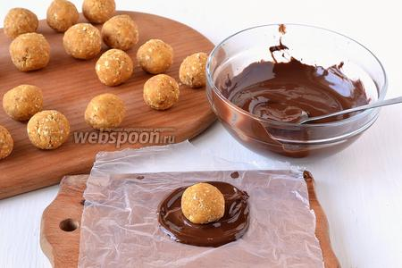 На небольшой квадрат пищевой плёнки выложить столовую ложку подготовленного шоколада. В центр выложить подготовленный тыквенный шарик.