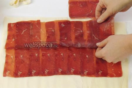 Сверху теста выкладываем половину тонкиx пластинок сыровяленой говядины так, чтобы они нахлёстывали одна на другую.