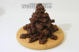 Для сборки ёлки расстапливаем столовую ложку шоколада и смазываем им каждую фигурку в центре. Выкладываем фигурки друг на дружку от большей к меньшей.