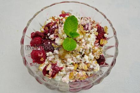 Сверху добавить сухой смеси сладких хлопьев. Полить тонкой струйкой жидкого мёда. Украсить ягодами малины и мятой. Подавать десерт к завтраку.