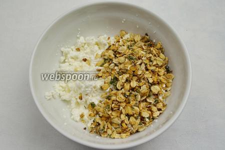 В творог добавить сухую смесь мятных хлопьев. Равномерно перемешать смесь ложкой.