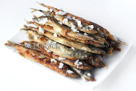 Ещё тёплую жареную мойву посыпаем измельчённым луком. Подаём мойву к картофельному пюре или другому гарниру.