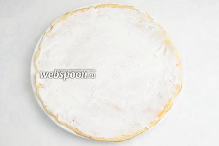 Резиновой кондитерской лопаткой или столовой ложкой равномерно нанести сырную массу тонким слоем на всю поверхность блина.