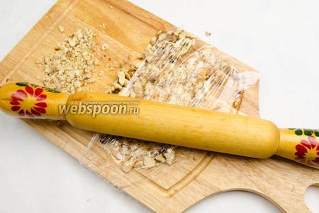 Измельчить орехи с помощью скалки, предварительно накрыв их пищевой пленкой.