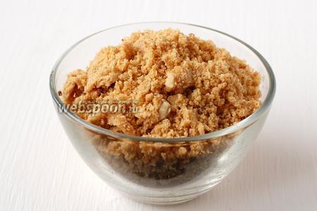 Тем временем с помощью кухонного комбайна измельчить арахисовый грильяж в мелкую крошку.