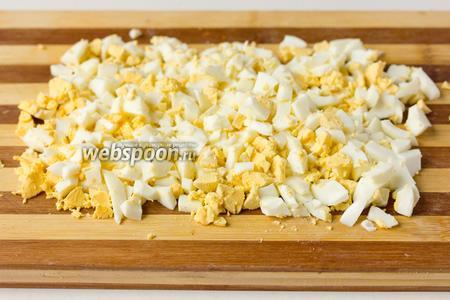 Нарезаем остывшие яйца небольшими кубиками (примерно так же, как и огурец), оставив один желток для украшения салата.