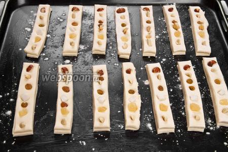 Выкладываем на каждую полоску сушённые фрукты и орехи, немного вдавливая их в тесто и ставим противень в тёплое место на 15 минут, чтобы подошло тесто.