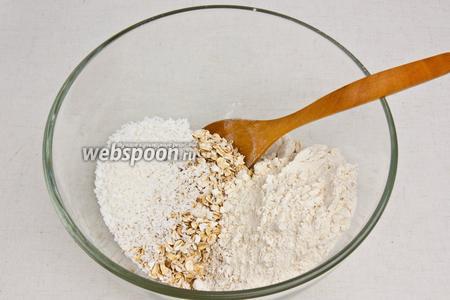 В отдельной посуде смешать муку, молотые овсяные хлопья, кокосовую стружку и ещё 50 г немолотых хлопьев.