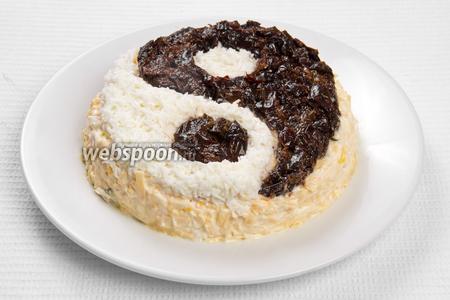 Теперь все ингредиенты выкладываем слоями, а каждый слой перемазываем майонезом: слои — курица, огурец, яичный желток, твёрдый сыр. Сверху, из яичного белка и чернослива, выкладываем знак «Инь-Ян». Салат готов, приятного аппетита!