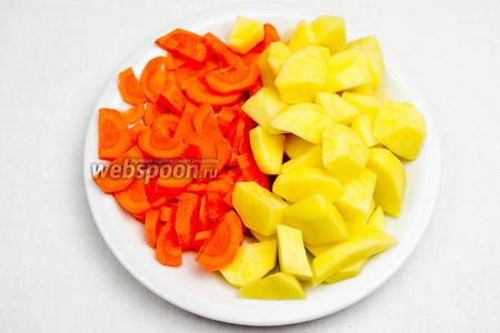 Картофель (3 шт.) и морковь (2 шт.) вымыть, почистить, нарезать картофель кубиком, а морковь полукольцами.