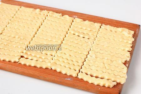 Раскатать тесто толщиной 0,4 см и порезать на полоски длиной 5-6 см и шириной 0,7 см.
