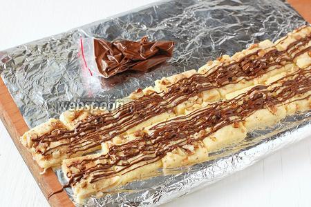 Отрезать в пакете уголок и нанести полоски шоколада на печенье. Охладить 20 минут в холодильнике.