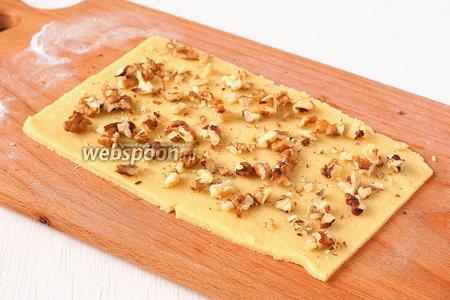 Раскатать тесто на подпыленной мукой доске толщиной 2 мм. Сверху выложить порезанные орехи.