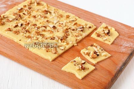 С помощью скалки прижать орехи так, чтобы они вошли в тесто. Порезать тесто острым ножом на квадратики размером 3х3 см.