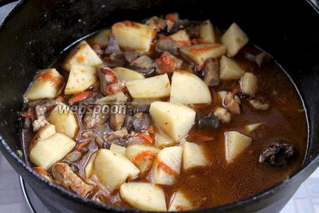 Добавить воды, лучше горячей — чтобы мясные продукты не затвердели, довести до кипения, убавить огонь до минимума и тушить под крышкой на медленном огне до полной готовности картофеля (около 40 минут).