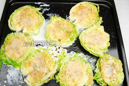 Выложить подготовленные капустные скибки на противень, полить сливками, ещё раз посыпать сухарями, поставить в горячую духовку. Запекать в течение 15-20 минут в режиме гриль.