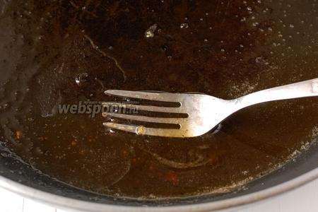 В сковороду с тёплой карамелью добавить ром.