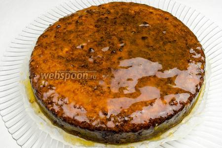 Остывший торт выложить на плоское блюдо и смазать верх и бока приготовленным конфитюром. Оставить торт для пропитки на 20-30 минут. Тем временем можно сделать украшение для торта — розы из кожуры апельсинов. Острым ножом очистить апельсины цельной полосой. Выложить полосу кожуры в форме цветка.