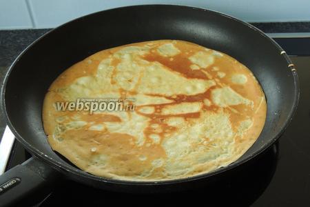 Затем выпекаем тонкие блины. Сковороду смажем маслом совсем чуть-чуть и на раскалённую, смотрите не пережгите масло, наливаем тонким слоем тесто, наклоняем сковороду в разные стороны, тем самым распределяя равномерно тесто. Как только тесто станет золотистым и самостоятельно отделяться от дна сковороды, переворачиваем на другую сторону (пропекание одного блина не более 1-1,5 минут). И так 36 штук — по 12 разного диаметра.