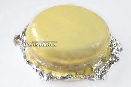 Под нижний корж подкладываем кусочки фольги, чтобы сохранить чистой тарелку. Заливаем торт белым ганашем, разглаживаем с помощью фена при средней температуре и низкой скорости.