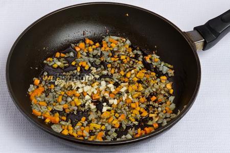 Добавляем в сковородку половину измельчённого чеснока и жарим 1 минуту.