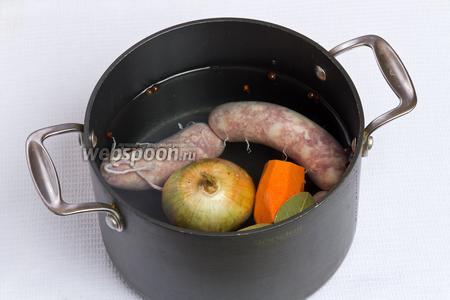 Теперь приступаем к приготовлению самого супа. Для этого кладём в кастрюлю колбасу, нечищенный лук, очищенную морковь, лавровые листы, гвоздику и перец горошком. Далее заливаем водой и варим 30 минут.