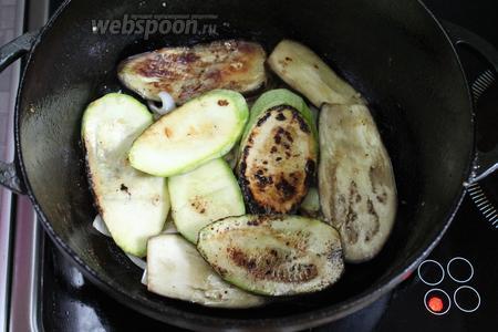Выключить плиту, включить духовку, нагреть её до 200°C. В казан на лук уложить слой подготовленных кабачков и баклажанов.
