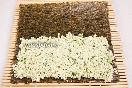 Нори положить на бамбуковый коврик и на каждый лист нори выложить примерно 3/4 стакана миндального сыра, полностью покрывая половину листа.