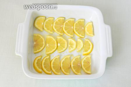 Дно формы для выпечки сбрызгиваем оливковым маслом, выкладываем дольки лимона. Если вы не хотите кислого картофеля, то можно положить меньше лимона или обойтись одним лишь маринадом.
