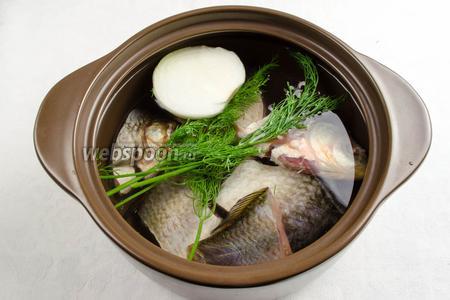 Рыбу выложить в кастрюлю. Добавить половину луковицы, веточки укропа.