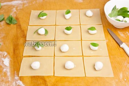 Слегка бумажным полотенцем промокнуть моцареллу и выложить на каждый квадрат по 1 шарику, затем положить по листочку базилика.