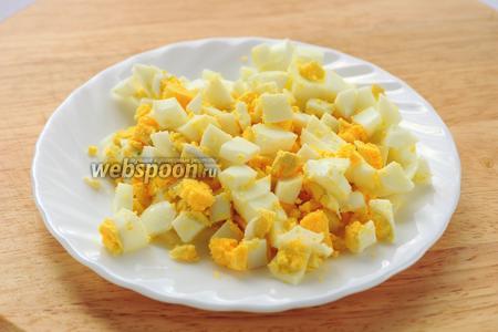 Предварительно отварить яйца, охладить и нарезать кубиками.