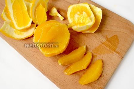 Филируем апельсин, обрезая корку вместе с белой частью. Затем вырезаем дольки между плёночными мембранами.