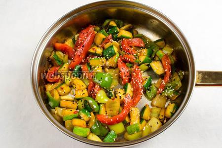 Посыпать на овощи семена кунжута и подержать на огне ещё 1 минуту.