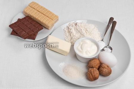 Основные ингредиенты: мука, масло, яйца, сахар, сметана, орехи, сода, ванилин, шоколад и вафли.